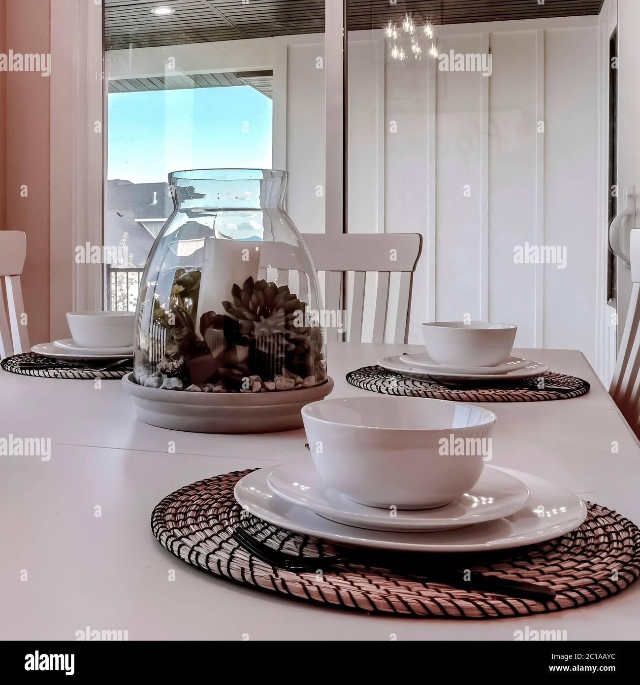 Square Dining Table With Chairs And Tableware Arranged Around A Decorative Centerpiece Stock Photo Alamy