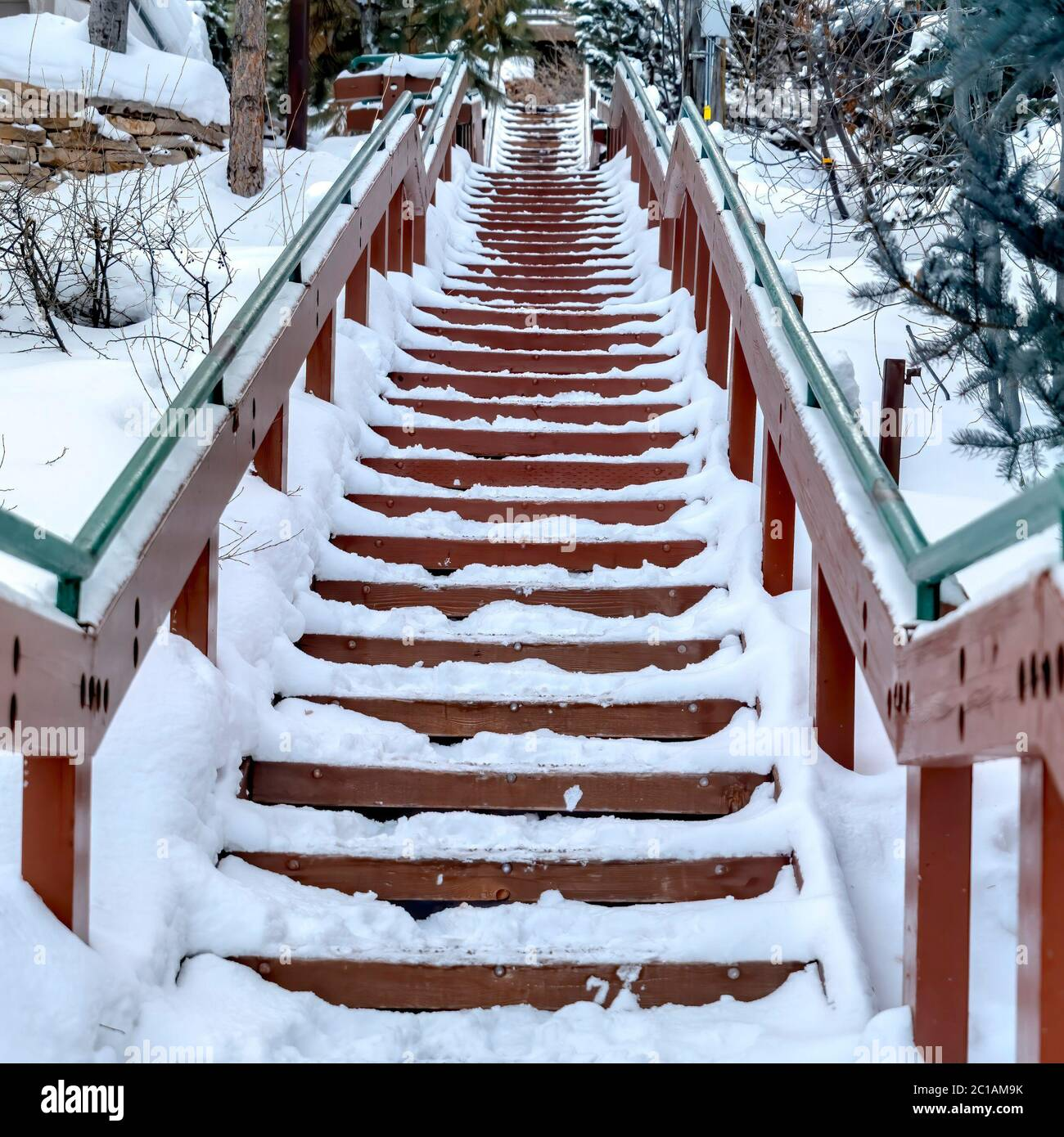 Square frame Focus on stairway that goes up a snowy hill with residential homes in winter Stock Photo