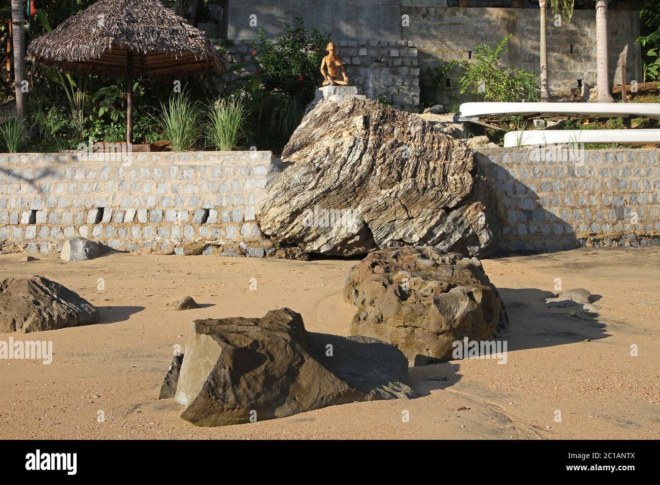 View of palm leaf-roofed lapa and wooden statue on 293 on Komba Guest House from the beach, Ampangorinana Village, Nosy Komba Island, Madagascar. Stock Photo