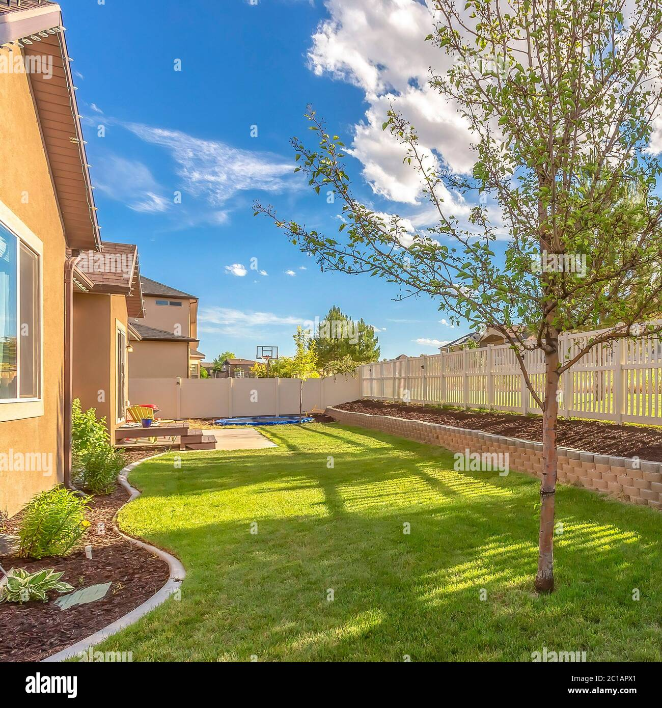 Square Home Backyard With Vibrant Lawn And Raised Planting Bed Along White Picket Fence Stock Photo Alamy
