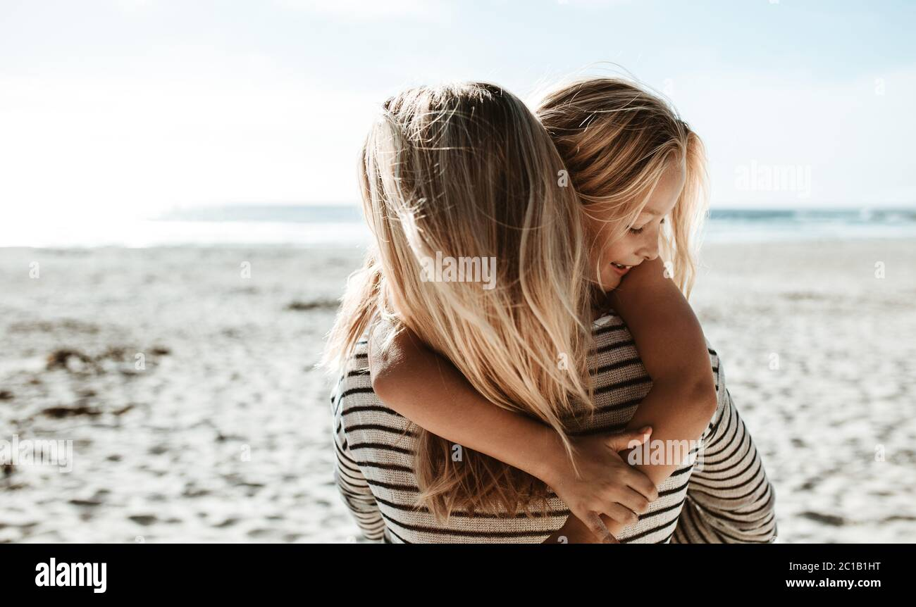 Rear view of a woman carrying her daughter and walking along the beach. Family on a summer beach vacation. Stock Photo
