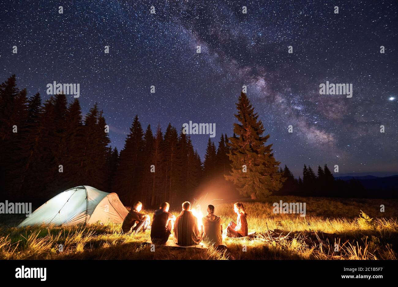 Night summer camping in the mountains, spruce forest on background, sky with stars and milky way. Back view group of five tourists having a rest together around campfire, enjoying fresh air near tent. Stock Photo