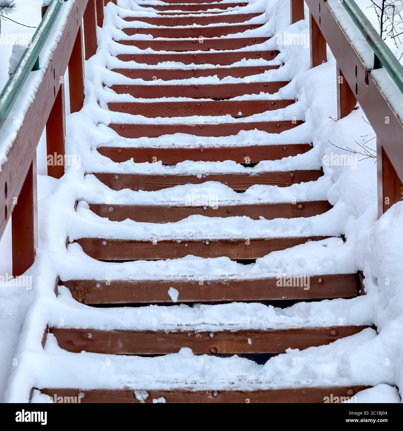 Square Focus on stairway that goes up a snowy hill with residential homes in winter Stock Photo