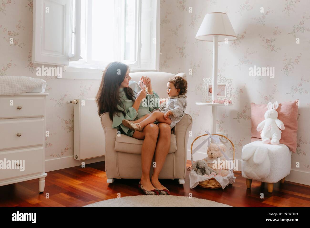 Pregnant young woman plays with her girl sitting in the room Stock Photo