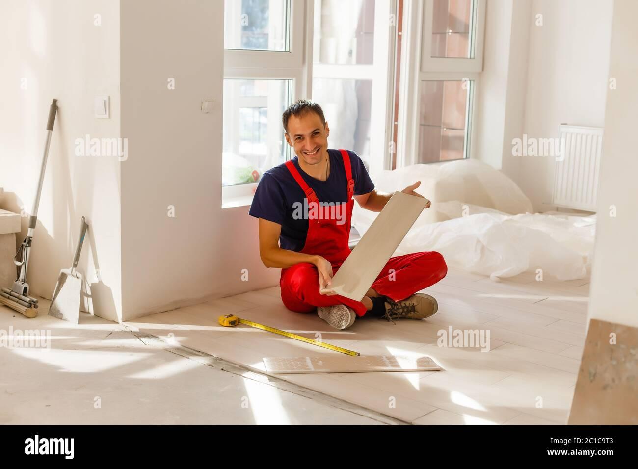Industrial Tiler Builder Worker Installing Floor Tile At Repair Renovation Work Stock Photo Alamy
