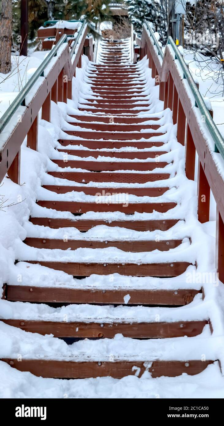 Vertical Focus on stairway that goes up a snowy hill with residential homes in winter Stock Photo