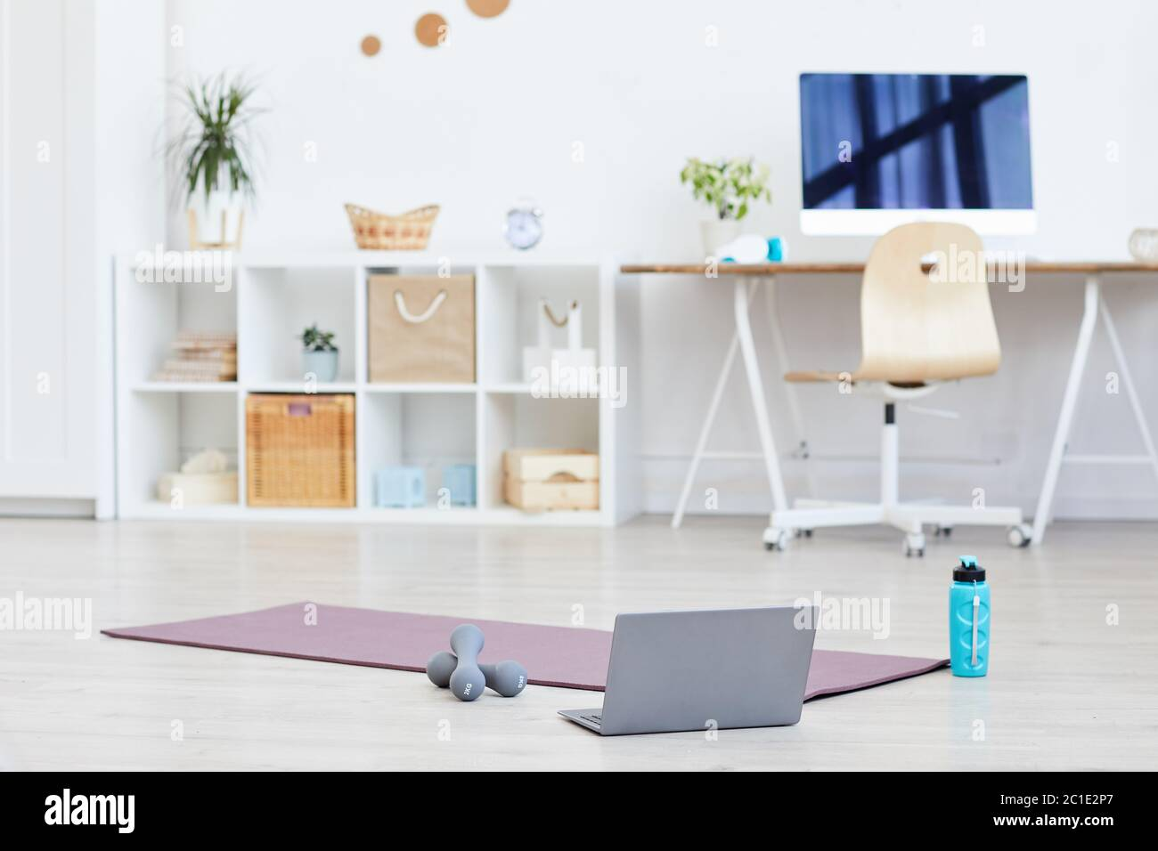 Exercise mat with dumbbells and laptop on the floor prepared for sports training at home Stock Photo