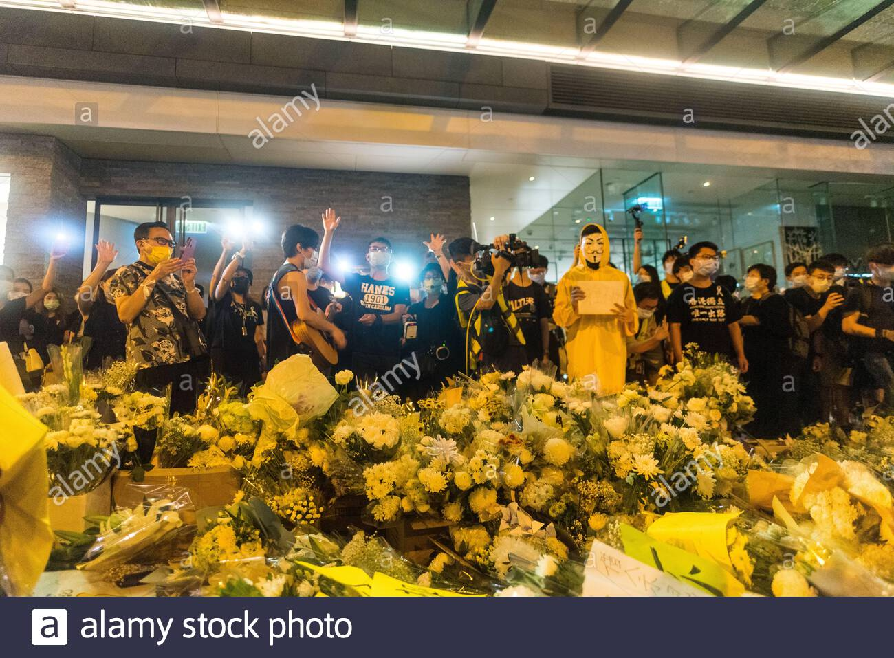 """Hong Kong, China. 15th June, 2020. Protesters make the sign """"five demands"""" in front of the flowers at the memorial for Marco Leung. Stock Photo"""