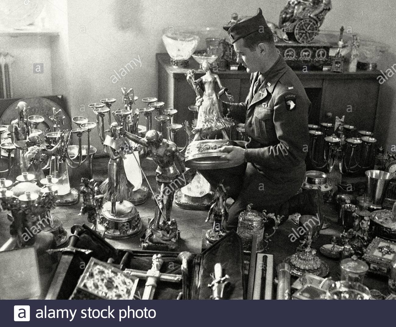 A U.S. soldier examines a solid gold statue, part of Hermann Goering's private loot, found by the 7th U.S. Army in a mountainside cave near Schonau am Stock Photo