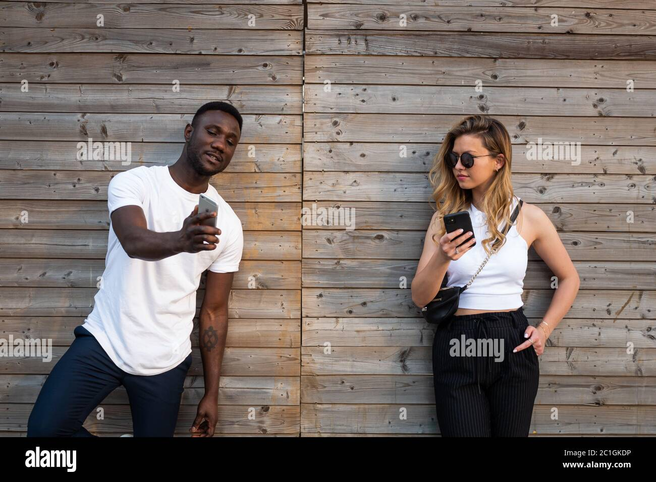 Young black man showing phone to blond caucasian woman wearing sunglasses. Medium shot. Front view. Stock Photo