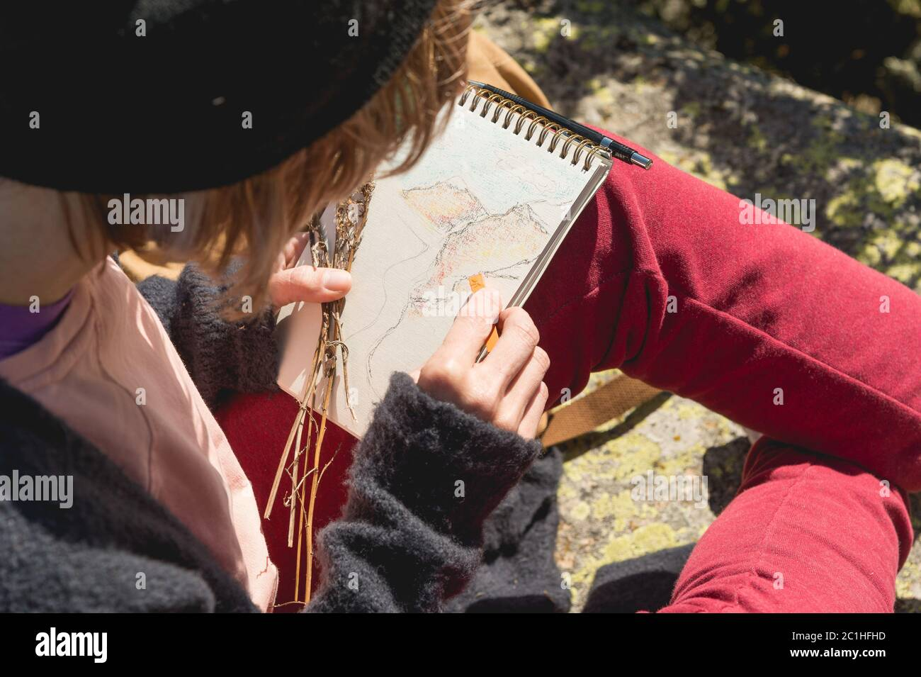 Stylish girl designer painter in the mountains sitting on a rock draws in a notepad at sunset Stock Photo