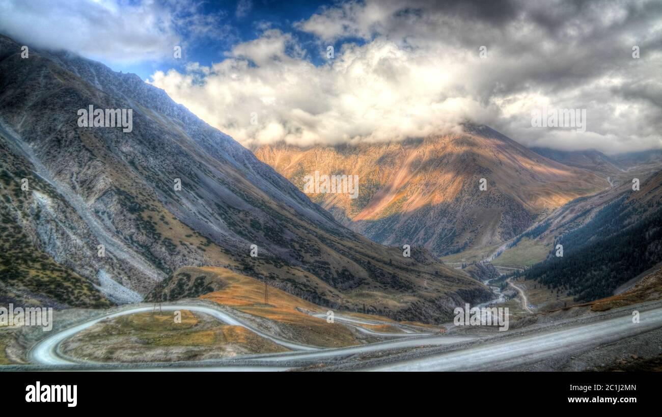 serpentine road to Barskoon pass, river and gorge and Sarymoynak pass, Jeti-Oguz, Kyrgyzstan Stock Photo