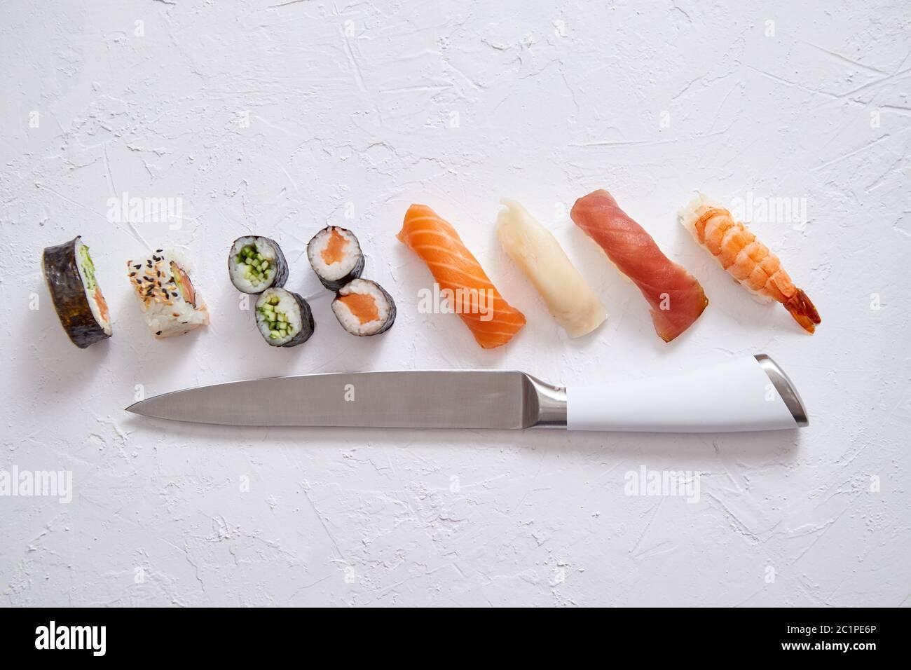 Various sushi rolls with Japanese knife on white stone slate background Stock Photo