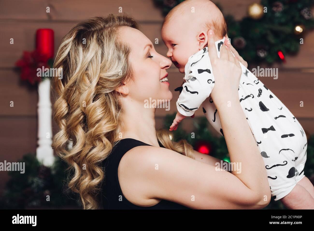 Boy with beautiful blonde mom embracing in decorated studio for Christmas. Stock Photo