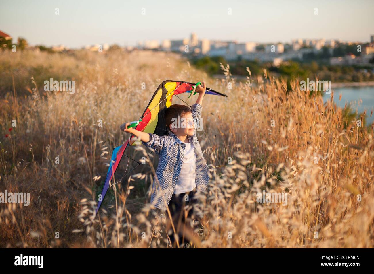 happy delightful smiling small kid with kite in hands standing on summer field nea sea port outside city Stock Photo