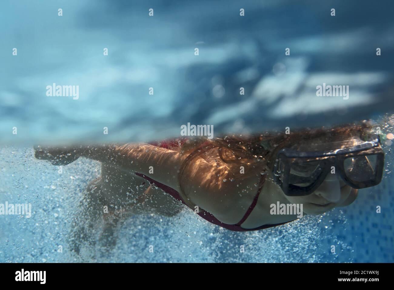 Blond child girl underwater swimming in blue pool Stock Photo