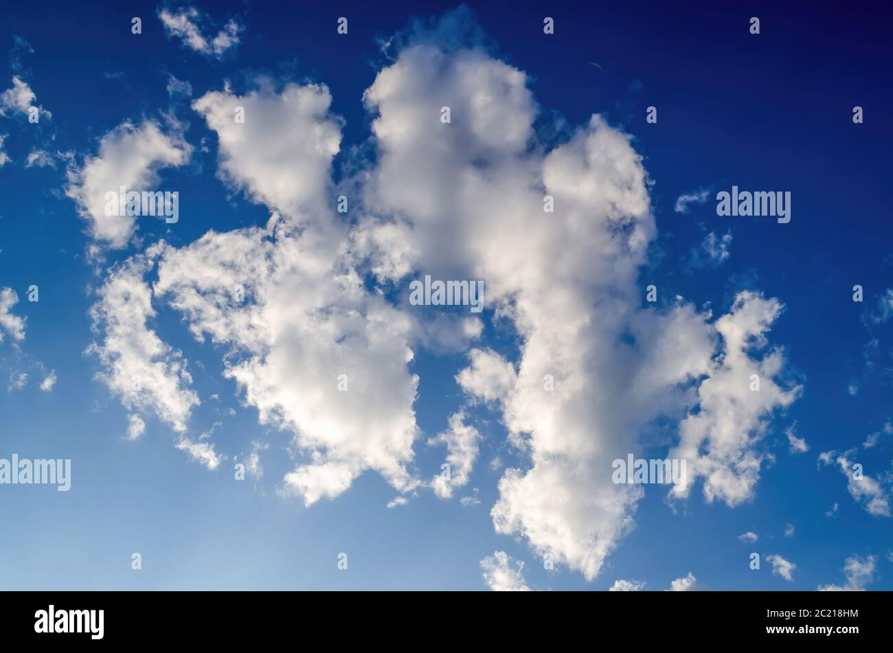 From below white fluffy clouds floating on bright blue sky on sunny day Stock Photo