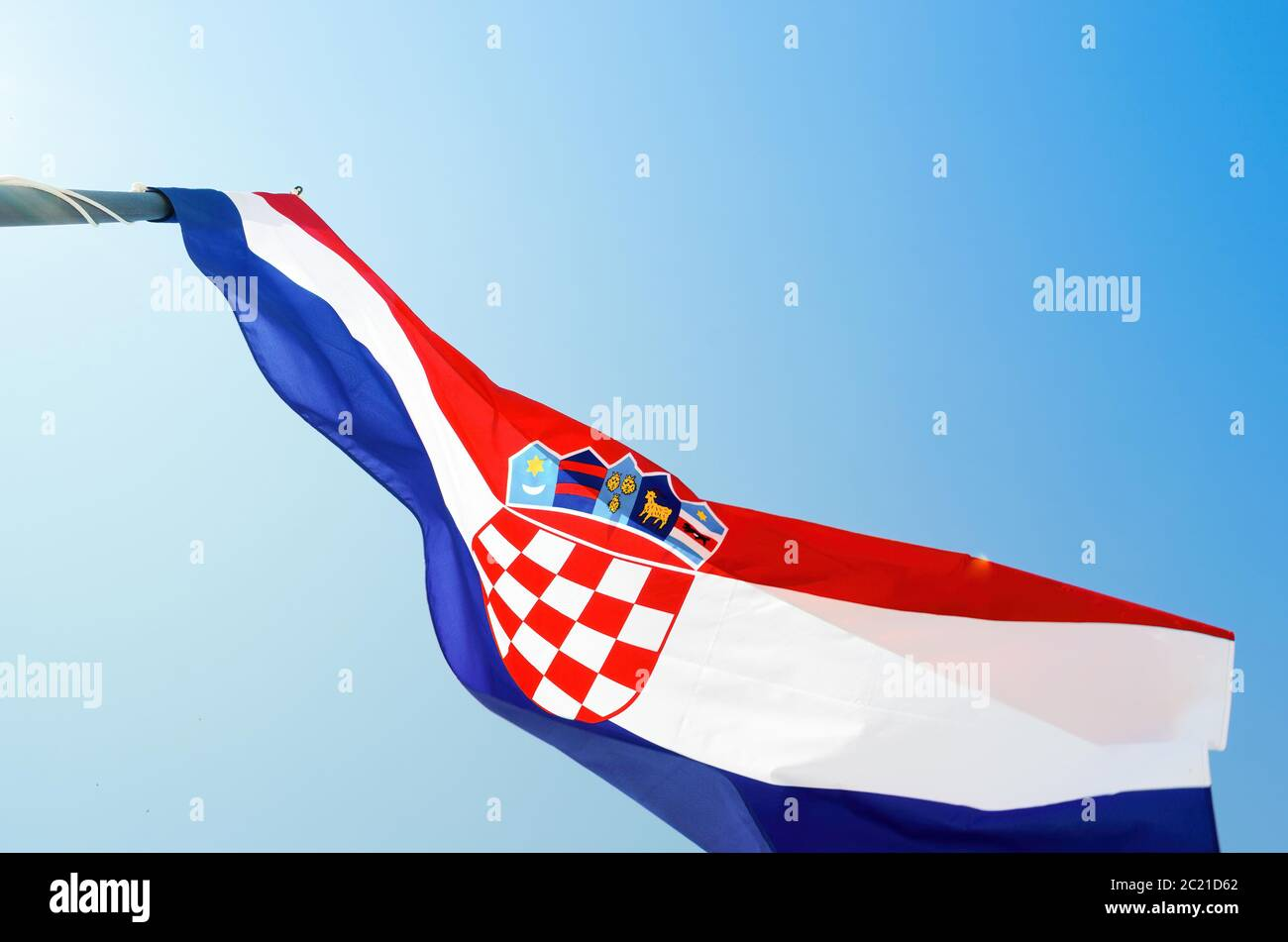 From below national flag of Croatia fluttering on wind against cloudless blue sky on sunny day Stock Photo
