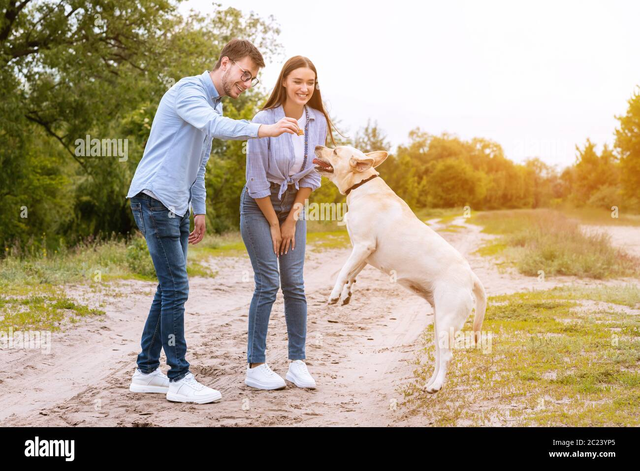 Young couple giving a treat to their happy dog Stock Photo