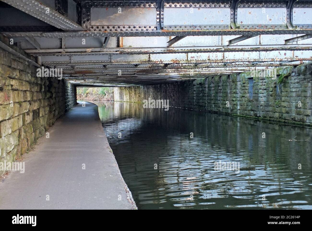 view under an old low steel girder bridge crossing the leeds to liverpool canal near armley with stone wall and a narrow footpat Stock Photo