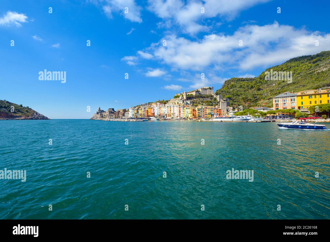 A speed boat crosses the colorful harbor of the village of Portovenere, Italy, on the Ligurian Coast near Cinque Terre. Stock Photo