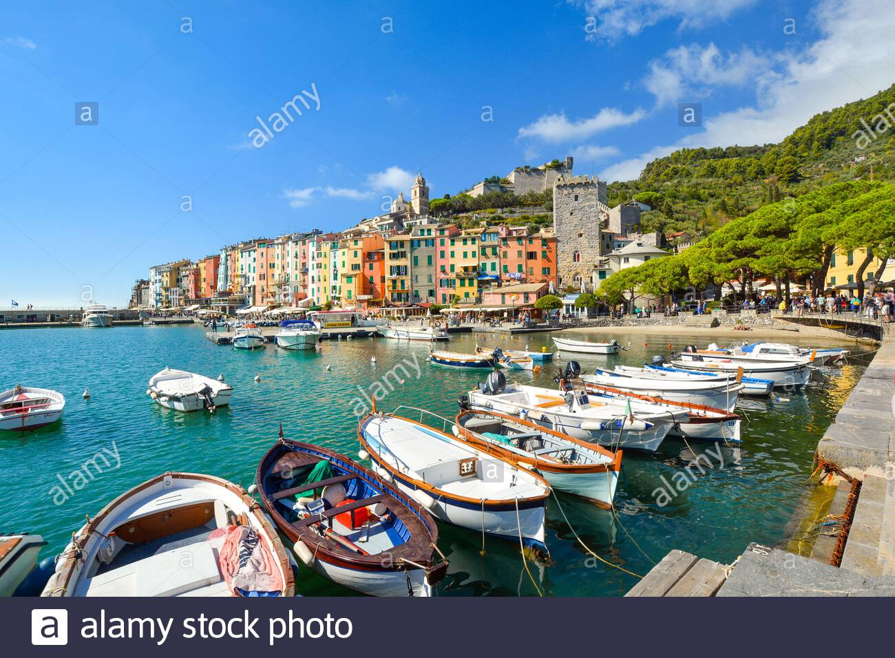 A row of boats in the harbor and pier at the colorful village of Portovenere, Italy, on the Ligurian coast, an Unesco World Heritage Site. Stock Photo