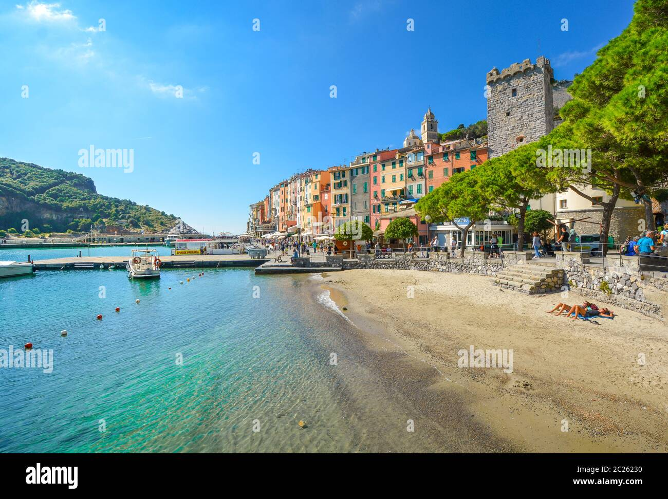 Tourists sunbathe on a sandy beach and walk the boardwalk at the seaside village and resort town of Porto Venere, Italy, an Unesco World Heritage site Stock Photo