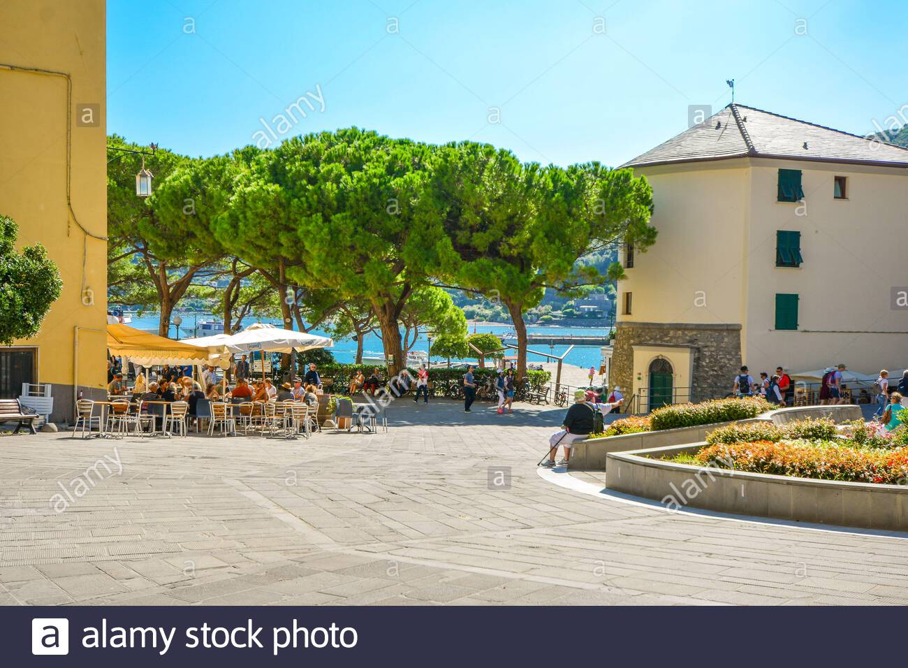 A sunny day on the Ligurian Coast as tourists enjoy cafes and relaxation on the  Piazza Bastreri in the coastal village of Portovenere, Italy Stock Photo