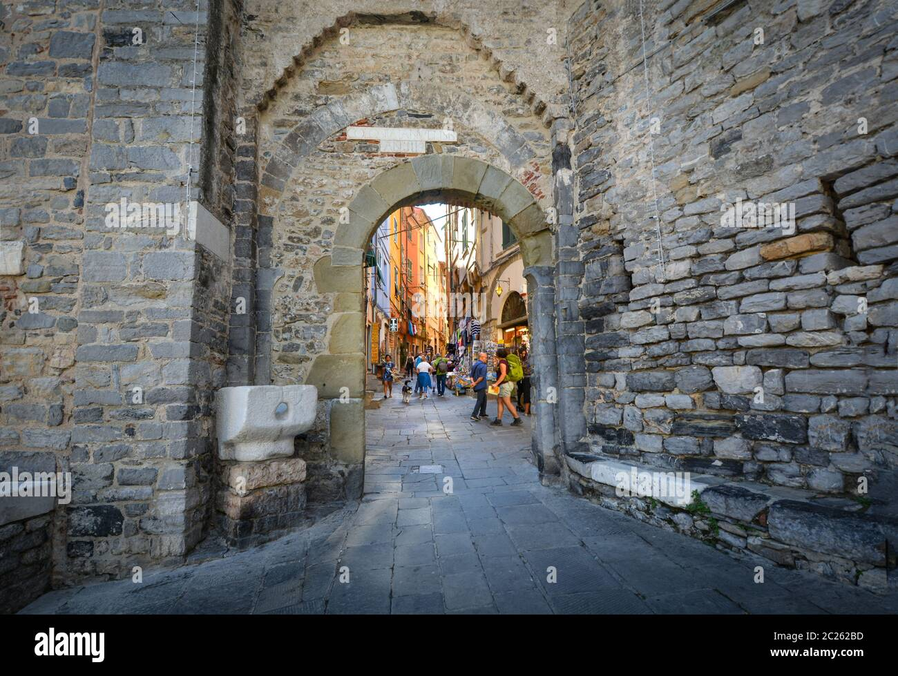 Tourists sight-see and shop inside the ancient town gate of the coastal village of Porto Venere, on the Ligurian coast of Italy. Stock Photo