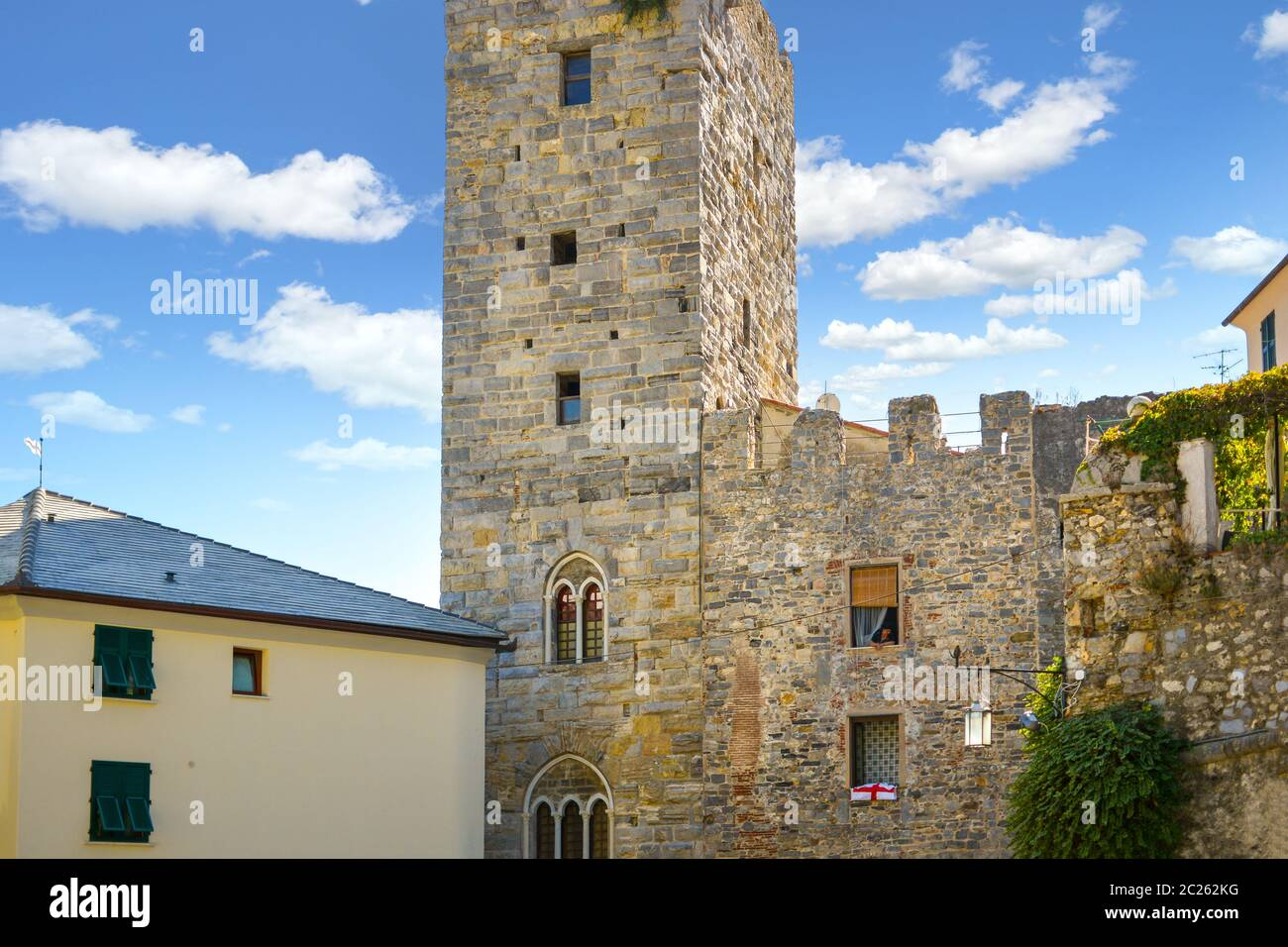 An Italian woman leans out from her apartment window in a medieval tower along the ancient walls of the city of Portovenere, Italy Stock Photo