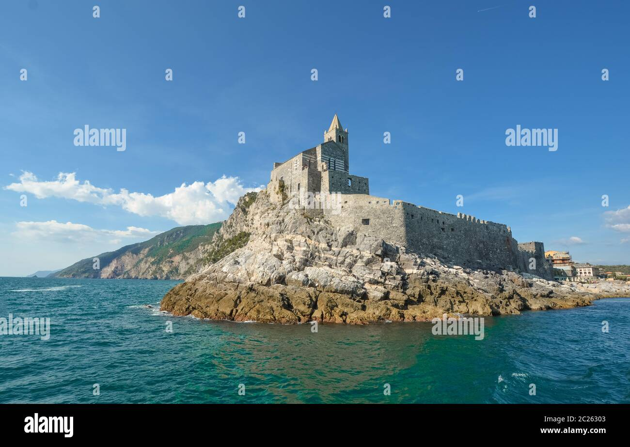 The imposing Church of St. Peter and the Doria Castle on the rocky peninsula at the entrance to Porto Venere Italy on the Ligurian Coast. Stock Photo