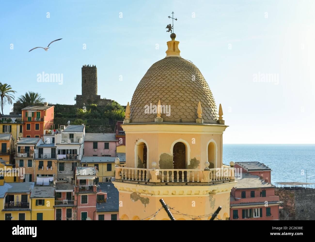 Tourists enjoy a beautiful view of the Ligurian Sea at the village of Vernazza Italy, part of the Cinque Terre, with the Santa Margherita church dome Stock Photo