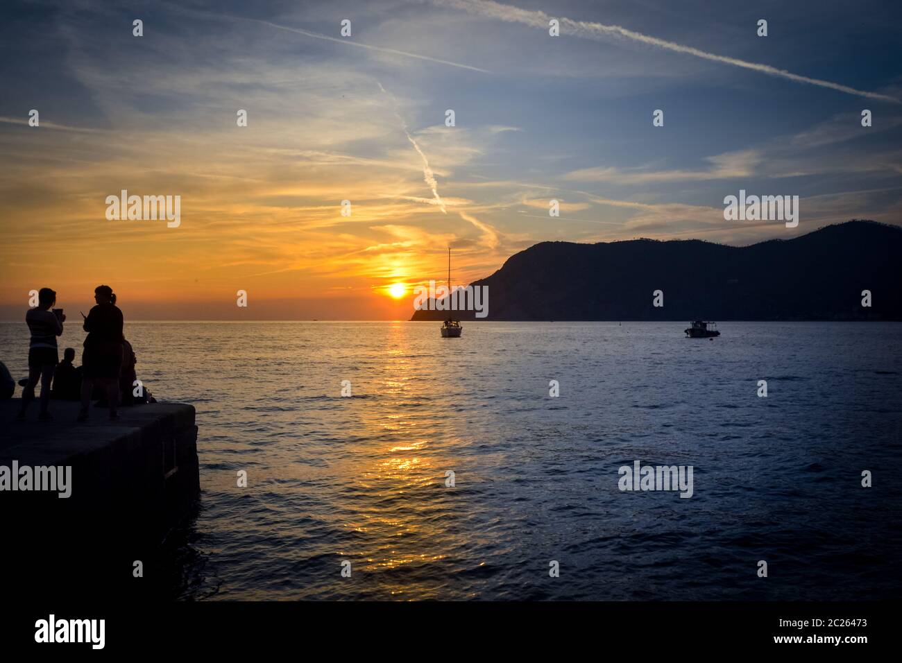 Two boats in the small harbor of Vernazza, Italy, as the sun sets on the Cinque Terre, on the Ligurian coast of the Italian Riviera Stock Photo