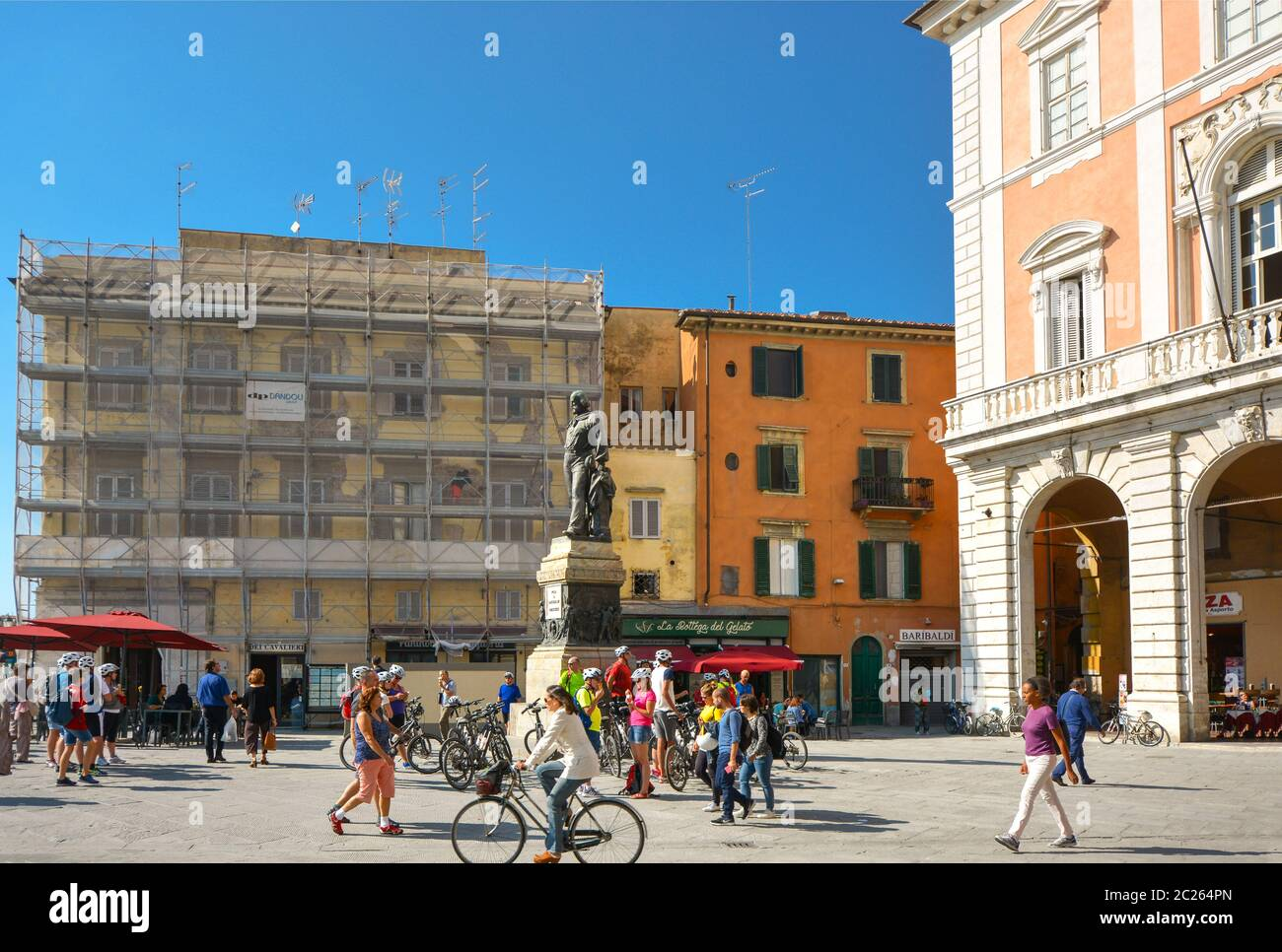 Tourists and locals, walking and on bicycles, enjoy a sunny day at Piazza Garibaldi in Pisa Italy with a statue of Giuseppe Garibaldi at the center Stock Photo