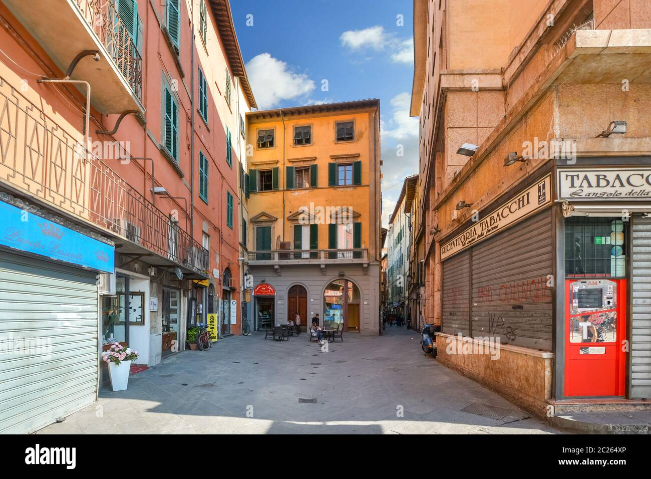 A very small sidewalk cafe opens for business alongside a narrow street in Pisa Italy Stock Photo