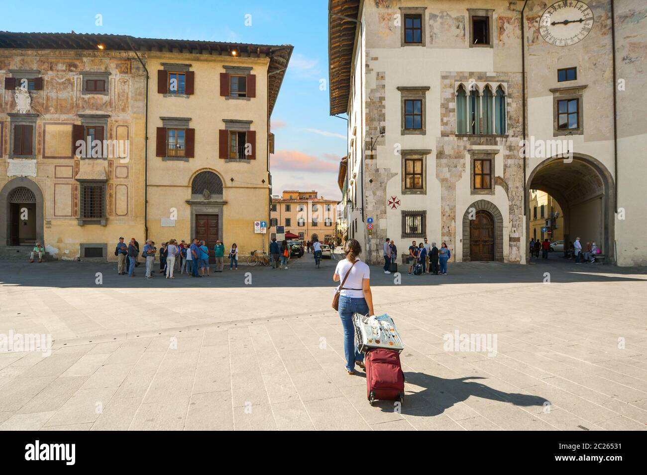 A female tourist traveling solo and pulling a luggage suitcase on wheels in the historic center of Pisa, Italy. Stock Photo