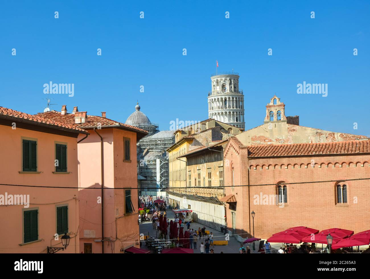 Tourists enjoy afternoon sightseeing on the Via Santa Maria, the busy tourist street leading to the Leaning tower of Pisa in the Tuscany area of Italy Stock Photo