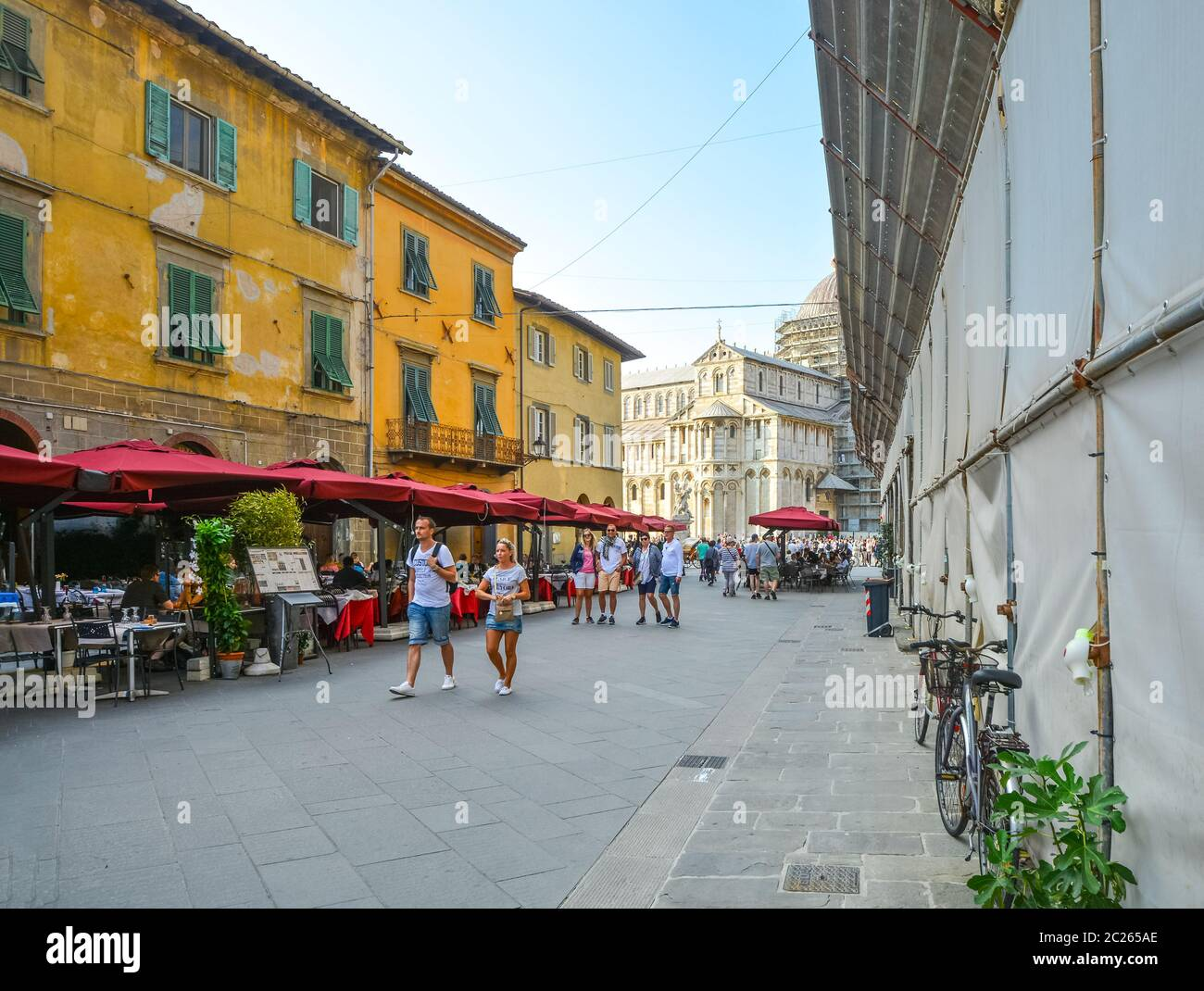 Tourists enjoy a late afternoon on the main street of cafes leading to the Pisa Square of Miracles, in the Tuscan city of Pisa, Italy Stock Photo