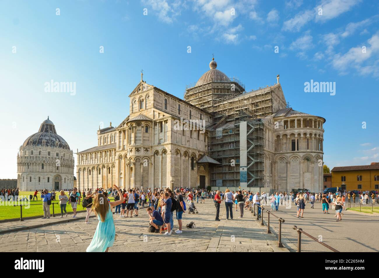 Tourists pose in front of the Pisa Duomo cathedral in the main piazza near the Leaning Tower in Pisa, Italy Stock Photo