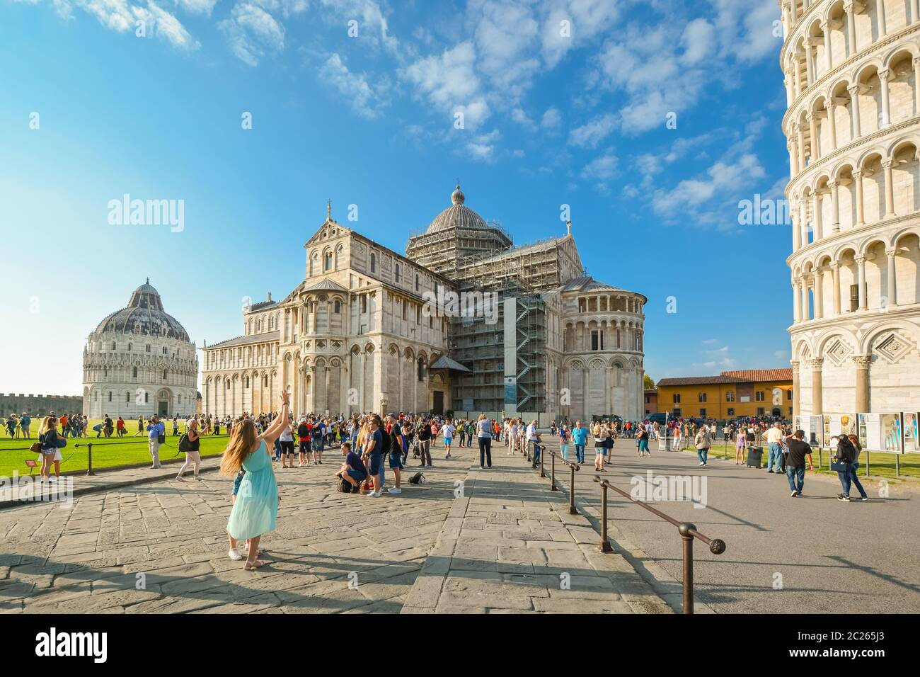 A female tourist poses in front of the Leaning Tower of Pisa with the Cathedral and Baptistery in view, Square of Miracles in Pisa, Italy. Stock Photo