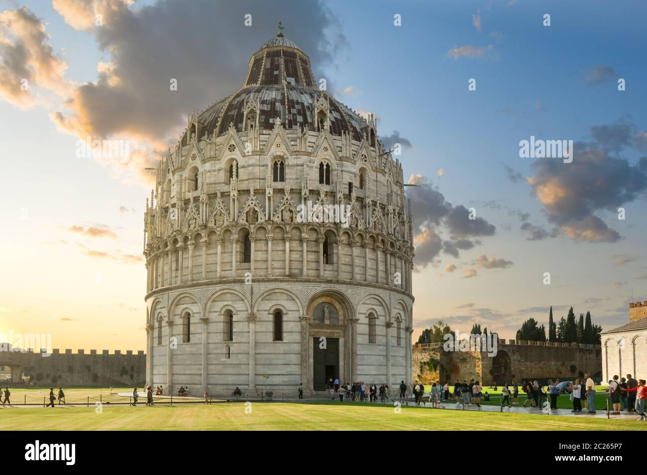 The historic, round Baptistery next to the tower and Duomo on the Field of Miracles, in the Tuscan city of Pisa Italy at sunset. Stock Photo