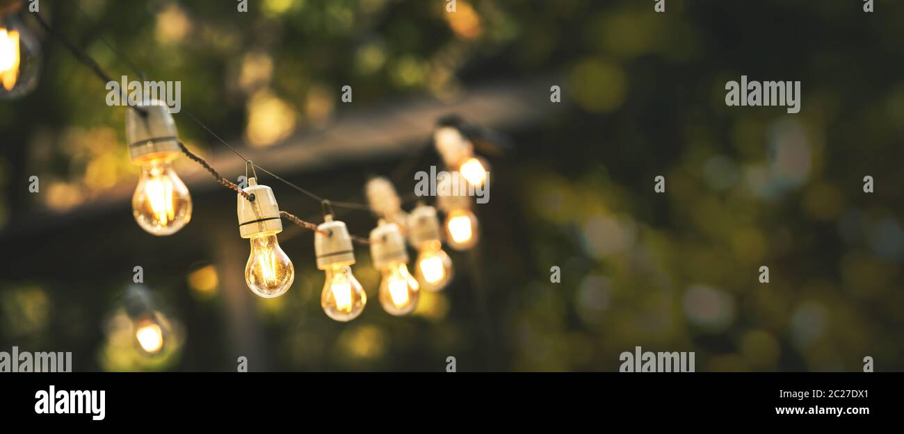 outdoor party string lights hanging in backyard on green bokeh background with copy space Stock Photo