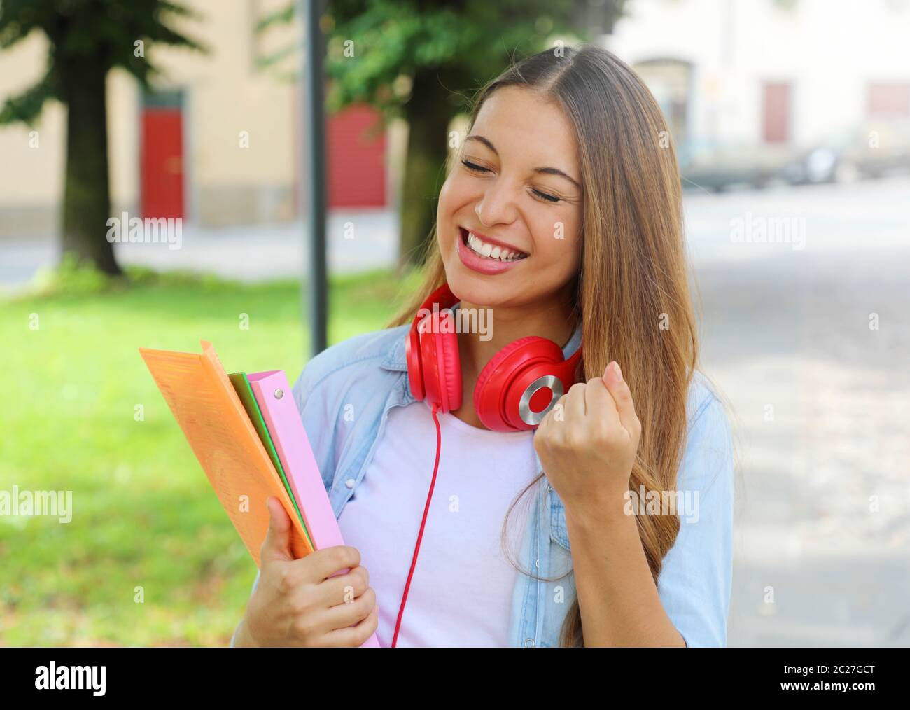 Portrait of excited laughing teenager girl with raising arm celebrating outdoors. Stock Photo