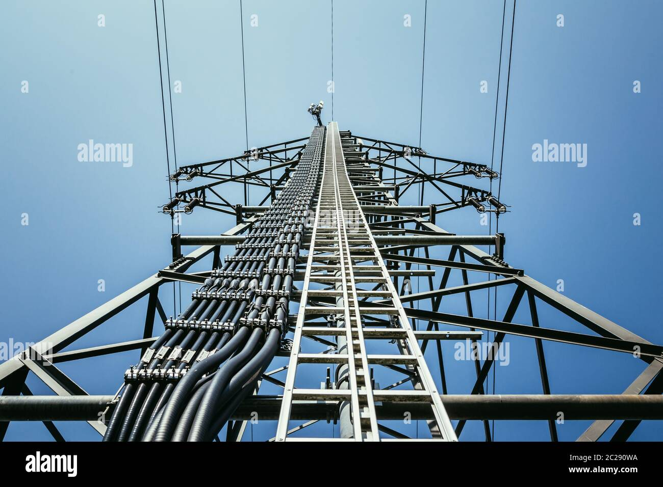 Close up of electrical tower and blue sky. Renewable energy and smart grid. Stock Photo