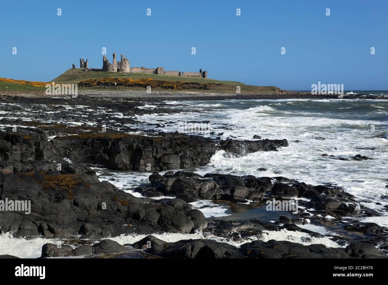 Rough seas below ruins of medieval Dunstanburgh Castle, Alnwick, Northumberland, England, United Kingdom, Europe Stock Photo