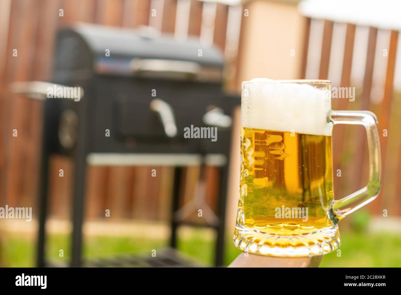Glass of fresh yummy beer on wooden armchair handle against blurred black on grilling machine in backyard Stock Photo