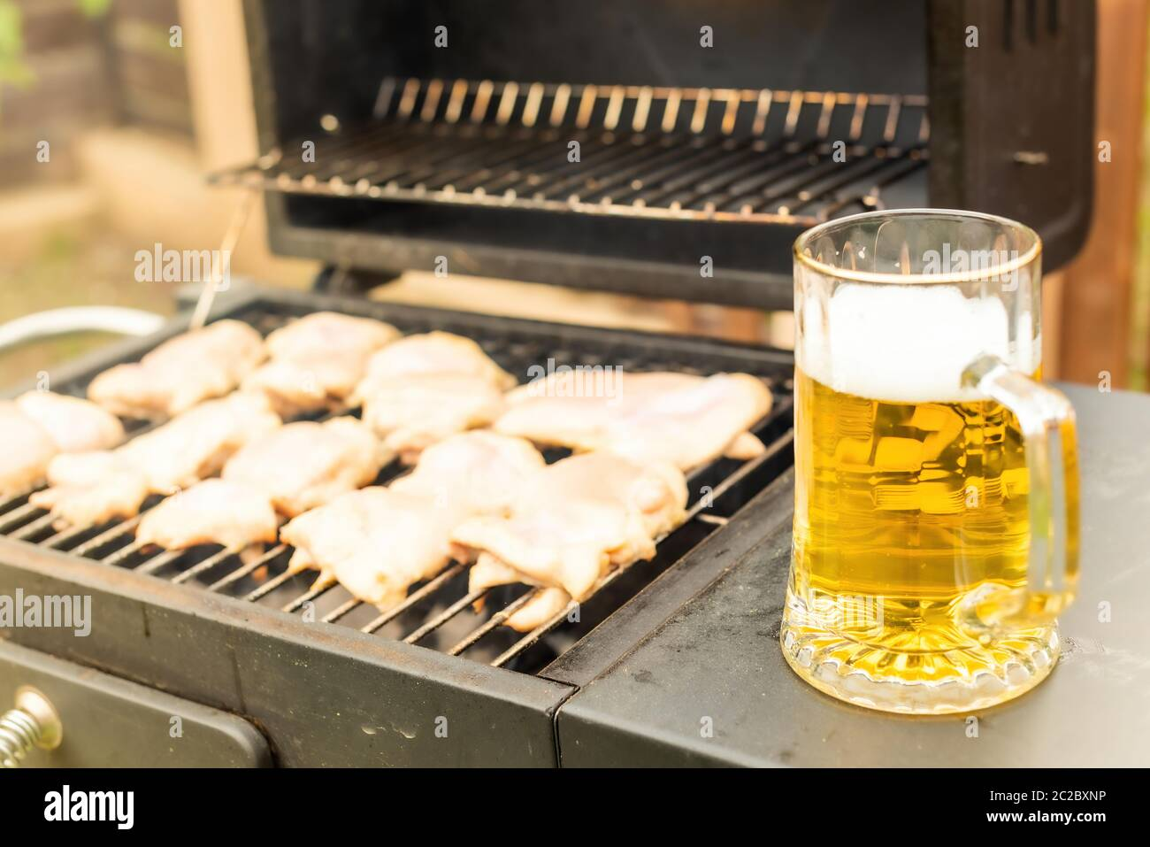 High angle of transparent jug of fresh fragrant beer beside pieces of meat roasting on grill machine in garden Stock Photo