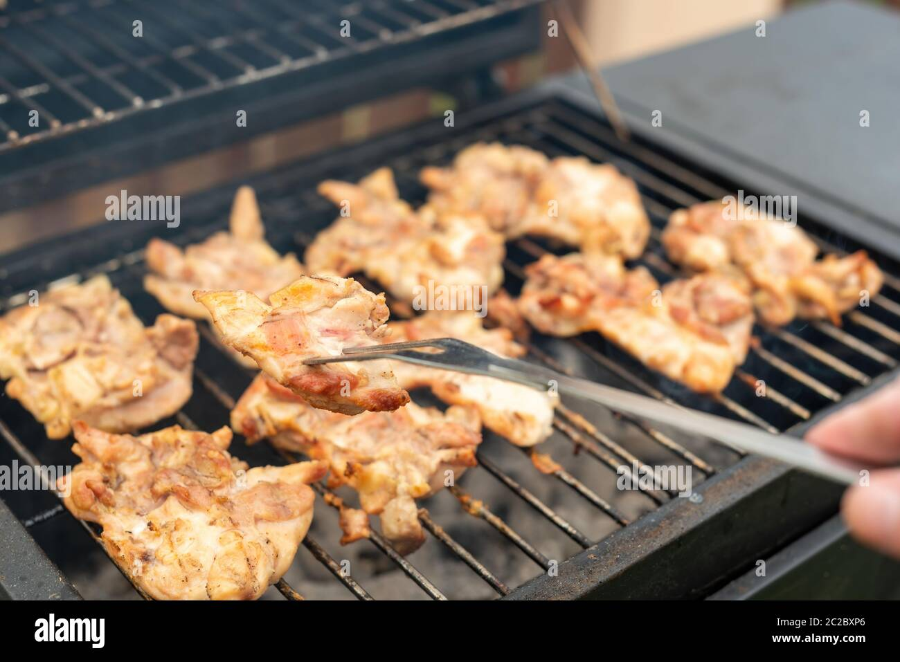 High angle of faceless cook holding big metal fork with piece of meat while roasting chicken thighs on grill in backyard Stock Photo
