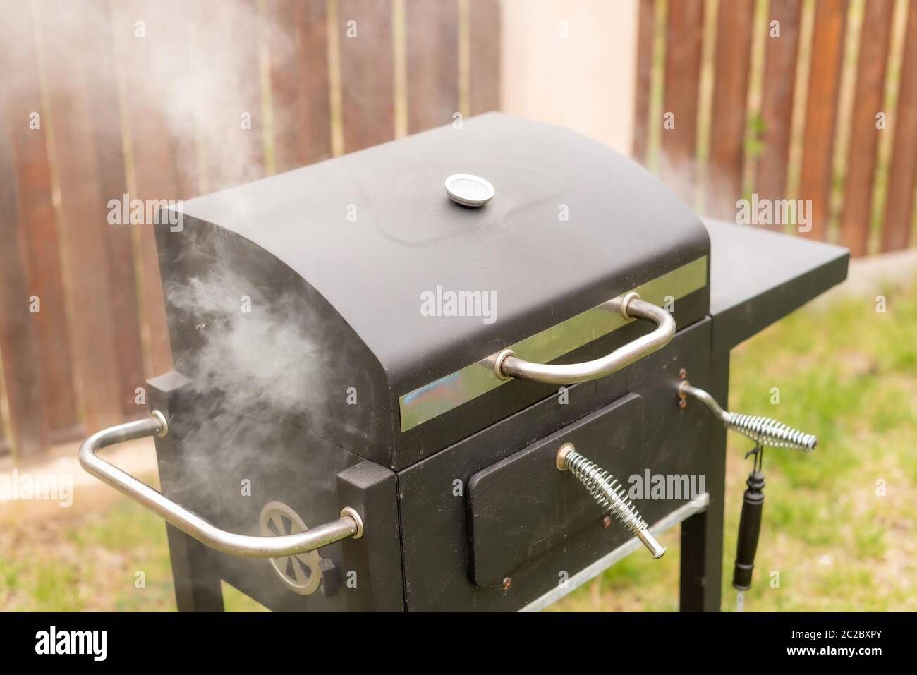 High angle of modern grill emitting smoke near fence during barbecue on summer day in garden Stock Photo