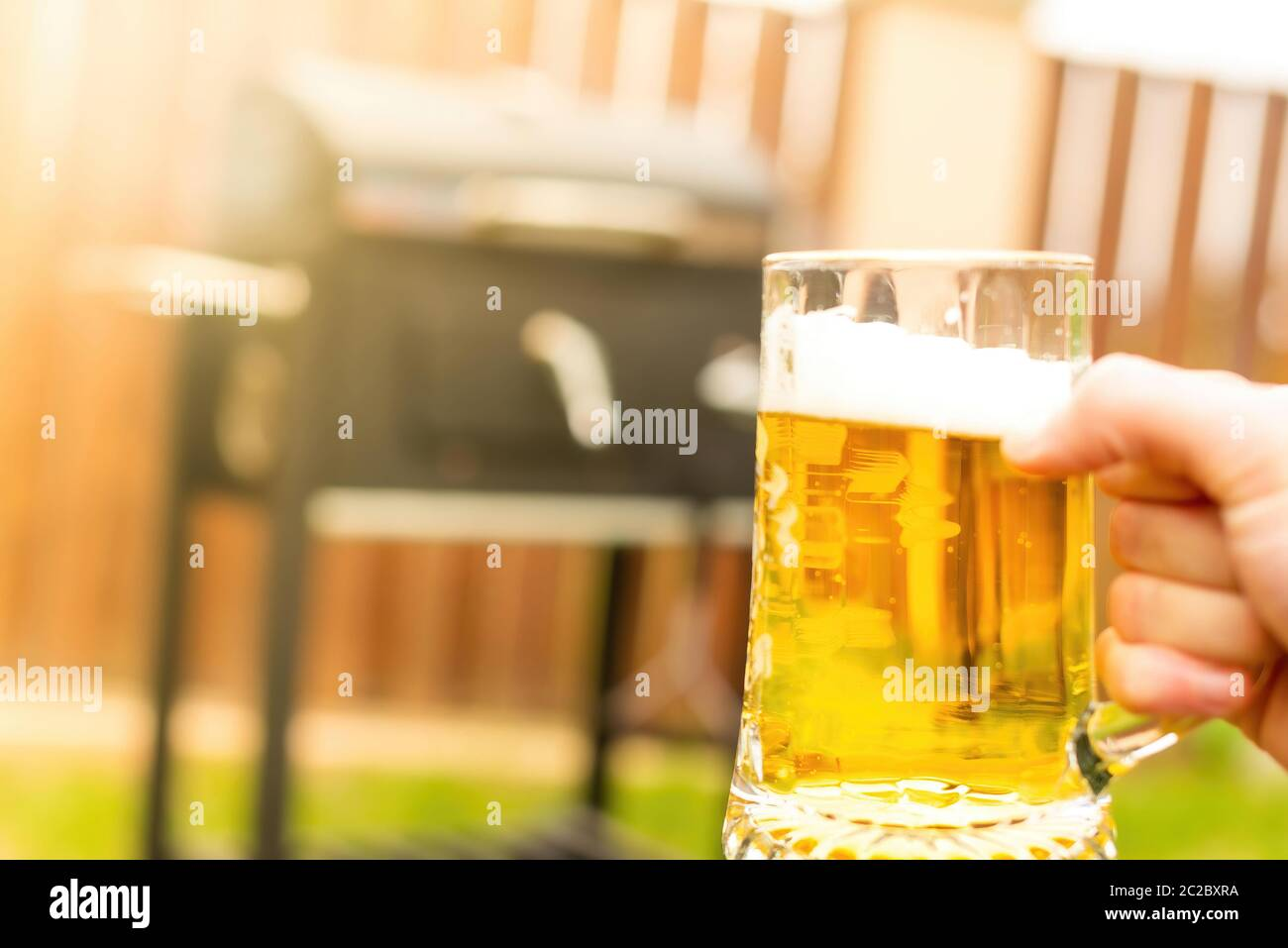 Unrecognizable person carrying mug of cold beer on blurred background of grill and fence during barbecue in yard Stock Photo